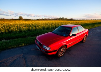 Rudershausen, Germany - April 30, 2018:25 year old car of the type audi 80 B4 with purified and rehashed red varnish on a small rural road in front of a yellow blooming rapefield