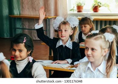 Rudka, Volyn / UKRAINE - April 29 2011: Blonde schoolgirl hand up sitting at school desk in rural school