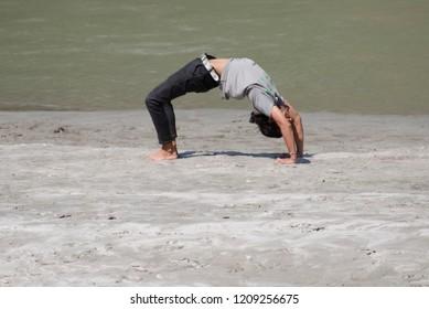 Rudra Prayag, Uttarakhand, India - September 30, 2018: Exercising or practising yoga on the bank of river Mandakini is quite Rejuvenating for health and mind.