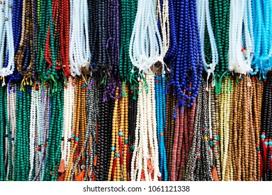 Rudraksha beads are hanging on the market. Background of the Rudraksha beads. Handmade colored stone necklace in market