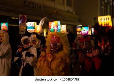 Ruemelinsplatz, Basel, Switzerland - March 11th, 2019. Close-up of piccolo players in their individual carnival costumes with illuminated head lanterns.