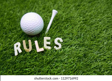 Rues of golf with golf ball and rules word on green grass