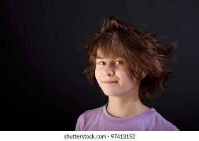 ruffled fun girl child on a black background. portrait