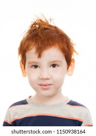 ruffled little boy with red hair on a light not isolated background, looks at the camera