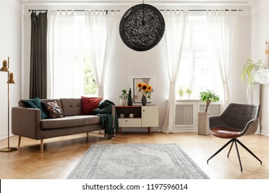 Rug between armchair and couch in living room interior with windows and sunflowers. Real photo