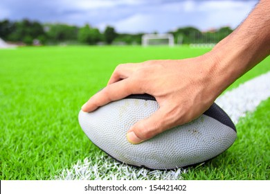 rugby ball in hand on green grass