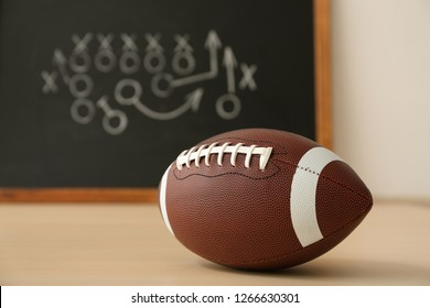 Rugby ball near chalkboard with football game scheme on table. Space for text