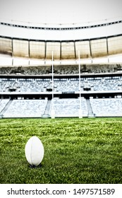 Rugby ball on the pitch against rugby ball stand in a stadium