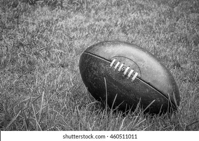rugby ball on rugby pitch grass with copy space. Black and white.