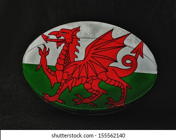 Rugby ball with Wales flag colors, over black background
