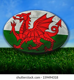 Rugby ball with Wales flag over grass