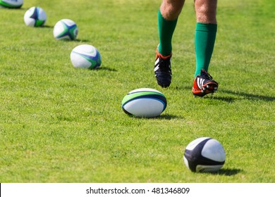 Rugby. Balls lying on pitch during workout. Closeup of legs running rugby player