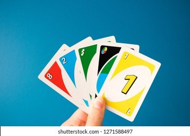 RUGBY, ENGLAND - JANUARY 1 2019: Uno game cards in female hand. American card game, teal background.