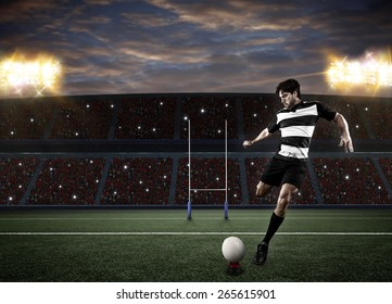 Rugby player in a black uniform kicking a ball on a stadium.