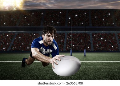 Rugby player in a blue uniform scoring on a stadium.