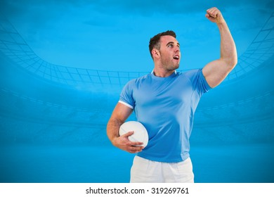 Rugby player cheering with the ball against blue background with vignette