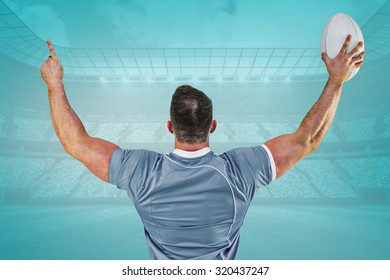 Rugby player cheering with the ball against blue vignette background