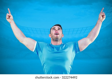 Rugby player cheering and pointing against blue background with vignette