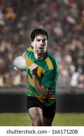 Rugby player in a green and gold uniform running on a stadium.
