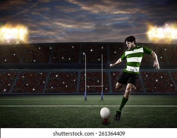 Rugby player in a green uniform kicking a ball on a stadium.