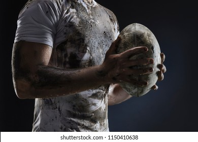Rugby player hands with ball on dark background. Close up