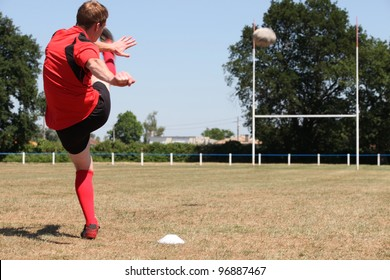 A rugby player kicking a ball