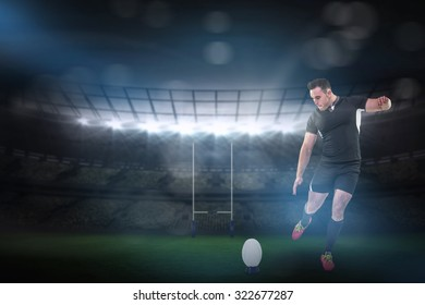 Rugby player kicking the ball against rugby stadium