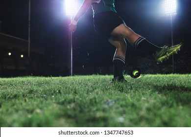 Rugby player kicking the ball from a tee for penalty shot. Legs of professional rugby player kicking the ball under lights at rugby stadium at night.