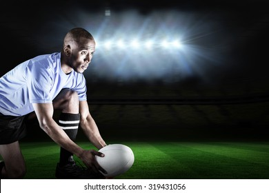 Rugby player looking away while keeping ball on kicking tee against rugby pitch