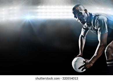 Rugby player looking away while holding ball against spotlight