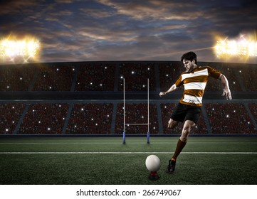 Rugby player in a orange uniform kicking a ball on a stadium.