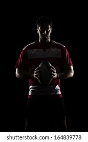 Rugby player in a red uniform. Black Background