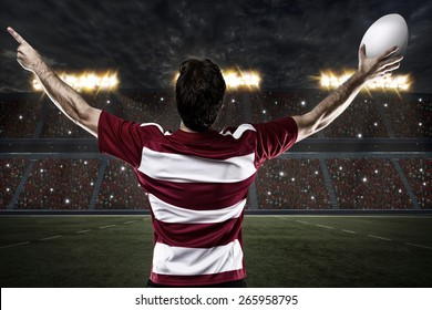 Rugby player in a red uniform celebrating on a stadium.