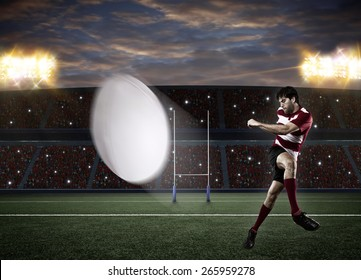 Rugby player in a red uniform kicking a ball on a stadium.