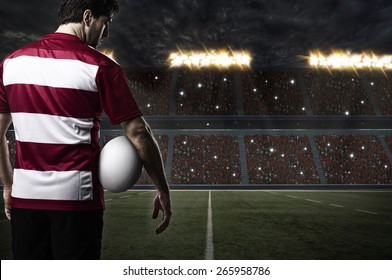 Rugby player in a red uniform on a stadium.