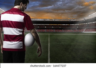 Rugby player in a red uniform in a stadium.