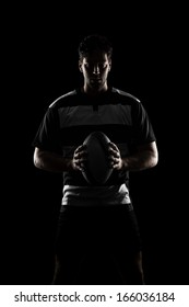 Rugby player silhouette in a black and white uniform. black Background