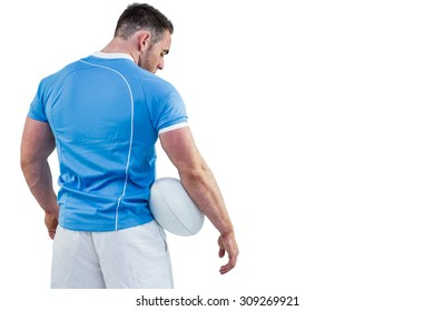 Rugby player standing with ball on white background