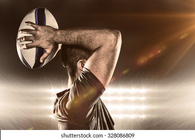 Rugby player throwing ball against spotlight