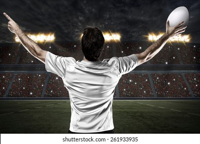 Rugby player in a white uniform celebrating on a stadium.