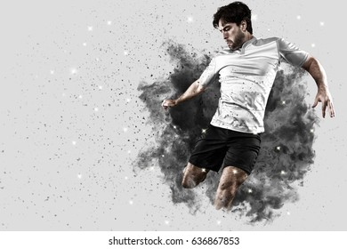 Rugby Player with a white uniform coming out of a blast of smoke .