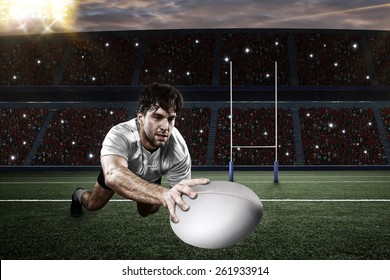 Rugby player in a white uniform scoring on a stadium.