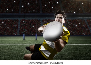 Rugby player in a yellow uniform scoring on a stadium.