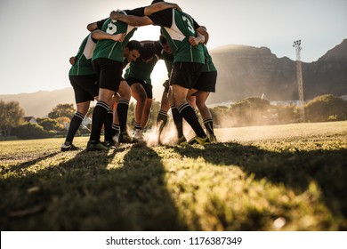 Rugby players in a huddle rubbing their feet on grass. Rugby team showing aggression after the win.