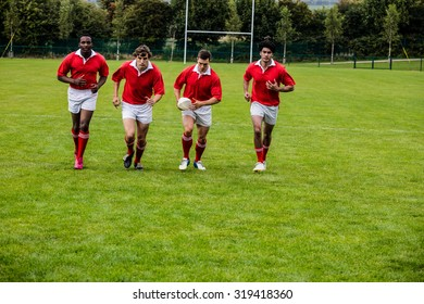 Rugby players jogging with ball at the park