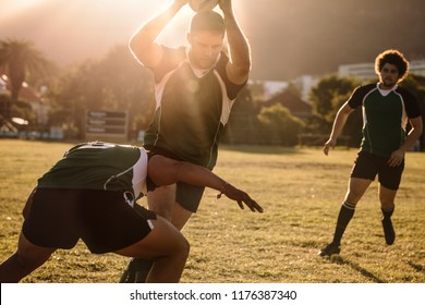 Rugby players running with ball and tackling during game. Rugby players fighting for ball in the match.