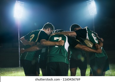 Rugby players standing together after the game under lights. Rugby team in huddle at sports arena at night.