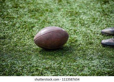 Rugby team player standing next to the ball. American football game.