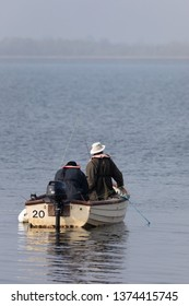 Rugby, Warwickshire / UK - April 18th 2019: Two anglers in a small boat with an outboard motor afloat on the water of a reservoir. The anglers face away from the camera towards a misty horizon.