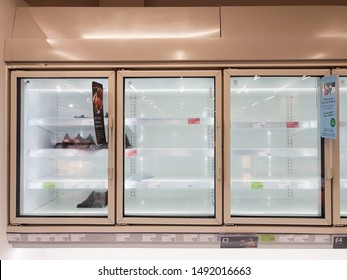 Rugby, Warwickshire / UK - August 20th 2019: Grass-fronted, wall-mounted, illuminated food freezer cabinets with empty shelves in the food section of a Marks and Spencer shop.